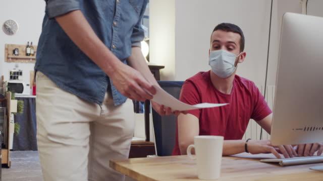 stockvideo's en b-roll-footage met slow motion video van twee collega's terwijl ze samenwerken in het kantoor, het dragen van beschermende gezichtsmaskers - heropening