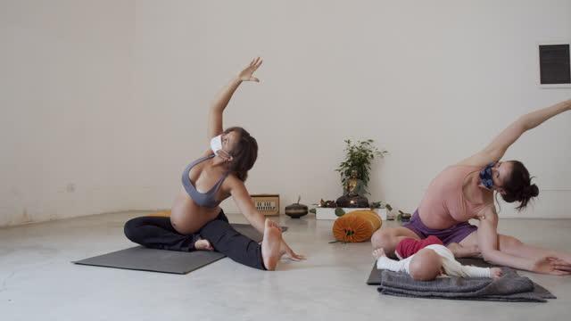 video al rallentatore di due amici che praticano yoga insieme, uno di loro è incinta e l'altro ha un bambino piccolo - incinta video stock e b–roll