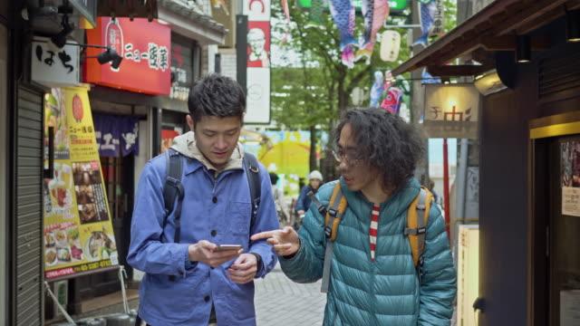 兩個朋友試圖找到一家有手機應用推薦的餐館的慢動作視頻 - 20多歲 個影片檔及 b 捲影像