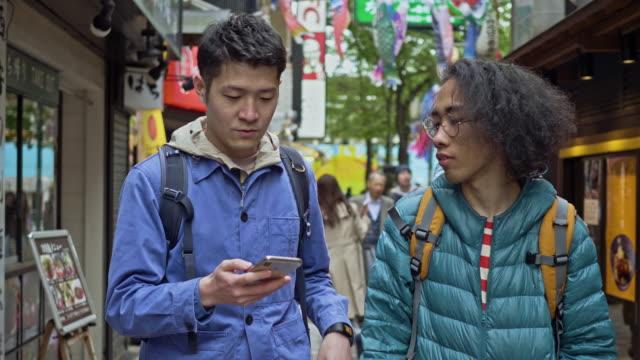 東京を訪れる2人の友人のスローモーションビデオ - バッグ点の映像素材/bロール