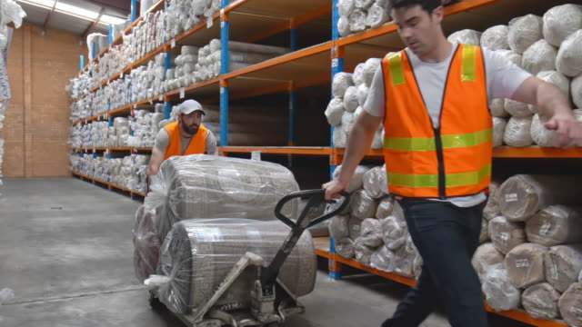 slow motion video of two men moving carpets in a warehouse - manual worker stock videos & royalty-free footage