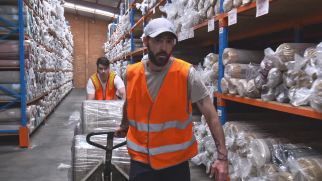 Slow motion video of two men moving carpets in a warehouse