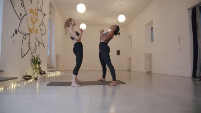 彼らはホイールで一緒にヨガを練習している間、2人の女性のスローモーションビデオ - urdhvaダヌラサナポーズ - 弓のポーズ点の映像素材/bロール