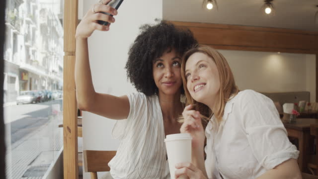 vídeos de stock e filmes b-roll de slow motion video of two young adult women taking a selfie together at the cafe - amizade feminina