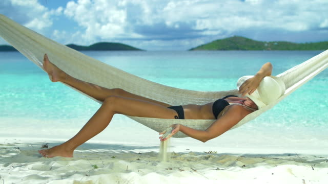 slow motion video of woman relaxing in beach hammock - hammock stock videos and b-roll footage