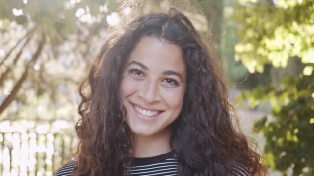 zeitlupenvideo von jungen erwachsenen frauen in einem öffentlichen park, öffnet ihre augen und lächelt - augen geschlossen stock-videos und b-roll-filmmaterial