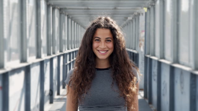 slow motion video of young adult woman in the city, opening her eyes and smiling - eyes closed stock videos & royalty-free footage