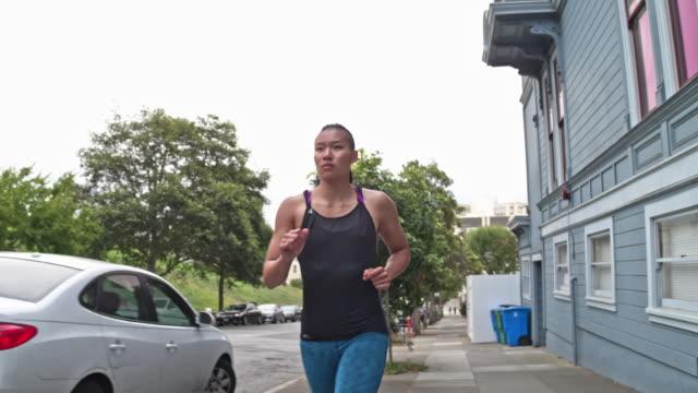 Slow motion video av ung asiatisk kvinna kör utomhus i San Francisco