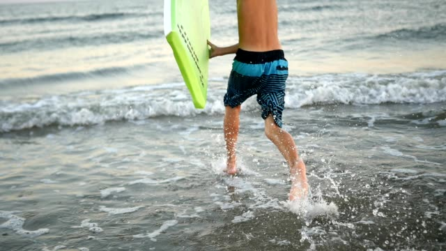 vídeos de stock e filmes b-roll de slow motion video of young boy with body board running into the ocean - 10 11 anos