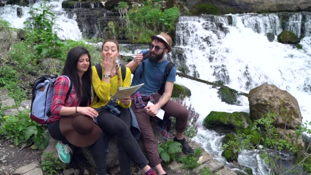 Slow motion video of young friends reading map while resting at the river bank