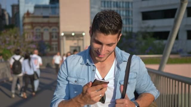 Slow motion video of young man holding mobile phone while walking in city