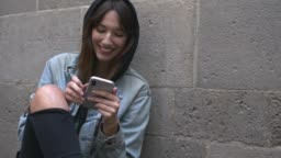 Slow motion video of young millennial woman reading a message on mobile phone