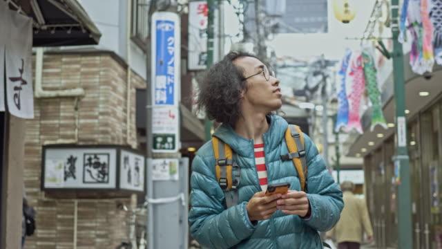 vidéos et rushes de vidéo de ralenti de jeune homme de course mixte regardant le téléphone mobile pour des directions dans la ville - être perdu