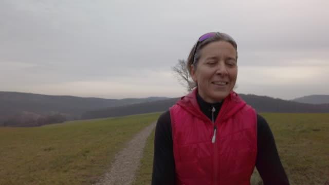 4k slow motion video, portrait front view woman jogging in rural landscape - mature women stock videos & royalty-free footage