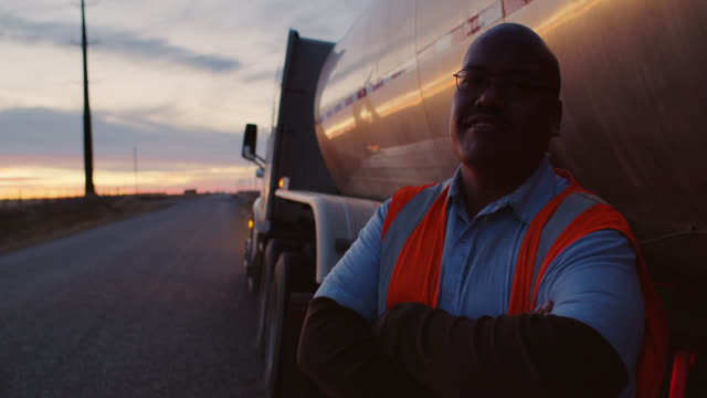 vidéos et rushes de slow motion video portrait of truck driver with arms crossed next to milk tanker trailer - vidéo portrait