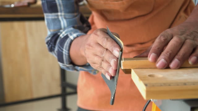 slow motion view: hands of a male carpenter sanding wooden plate in the workshop - sand stock videos & royalty-free footage