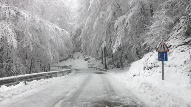 Slow motion view of a snowfall with big snowflakes taken from the car windshield on a roadtrip with nice snowy road.