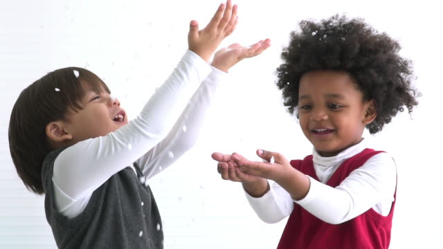 slow motion view of african boy and friend wearing winter cloth play artificial snow - warm clothing stock videos & royalty-free footage