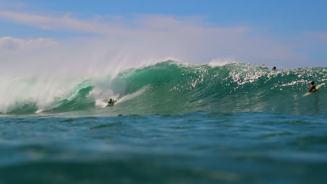 vídeos de stock, filmes e b-roll de slow motion view of bodyboarder catching wave from camera in the water - pipeline wave