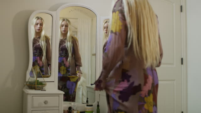 slow motion view of girl trying on dress in bedroom mirror / highland, utah, united states - vanity stock videos & royalty-free footage
