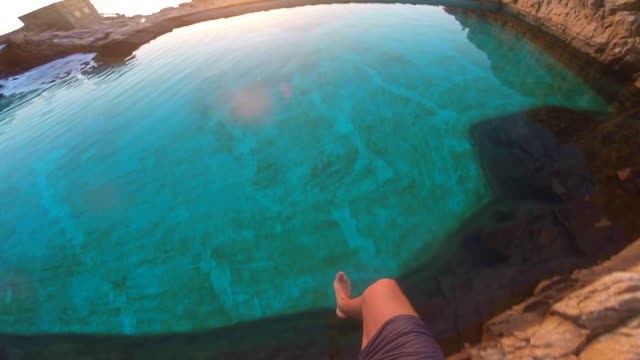 Slow motion view of guy from personal perspective jumping into a natural pool in the Mediterranean Sea Costa Brava shoreline on sunrise during summer time.