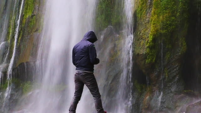 Slow motion view of hiker guy taking pictures with smartphone of a espectacular 100 meters tall waterfall in the Catalonia region.