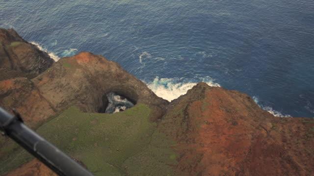 slow motion: view of ocean waves crashing on base of rocky hawaiian mountains, kauai, hawaii - ヘリコプター事故点の映像素材/bロール