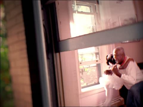 slow motion view through window of SOFT FOCUS Black girl in ballet tutu hugging kneeling senior Black man