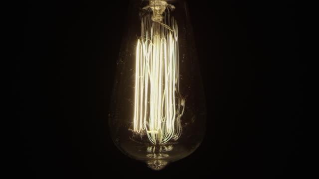 Slow motion vintage fashion electric light bulb black backgrounds swinging
