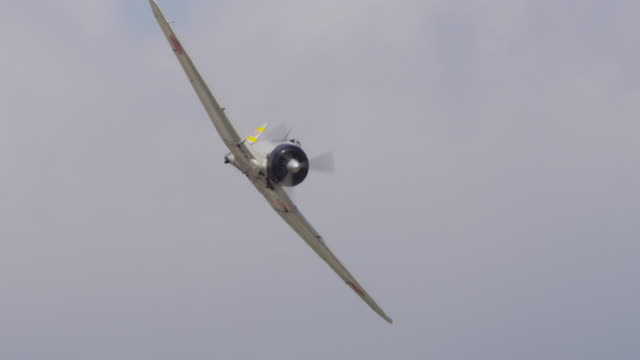 Slow motion vintage Japanese A6M Zero military prop fighter plane flies through the sky.