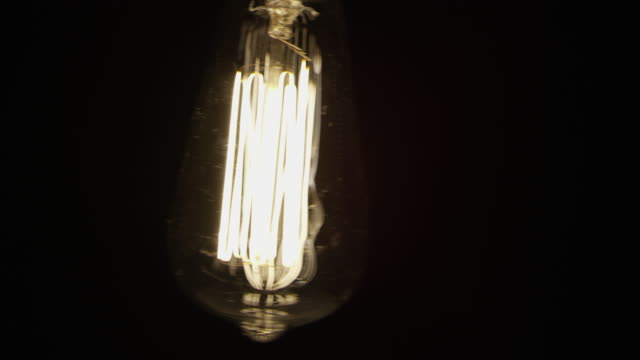 slow motion vintage old fashion black background electric light bulb - old lightbulb stock videos and b-roll footage
