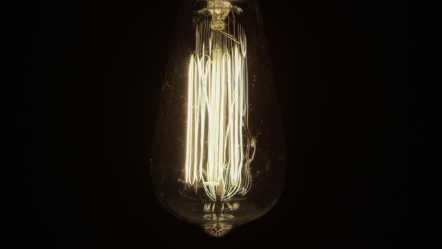 slow motion vintage old fashion electric light bulb black background - elettricità video stock e b–roll