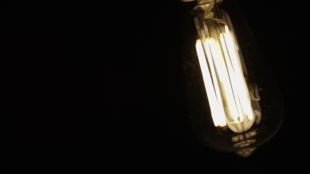 Slow-Motion Vintage Mode elektrisches Licht Lampe schwarzen Hintergrund schwingen