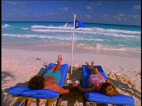 vídeos y material grabado en eventos de stock de slow motion waiter bringing drinks to couple on chairs on beach / cancun - tumbona