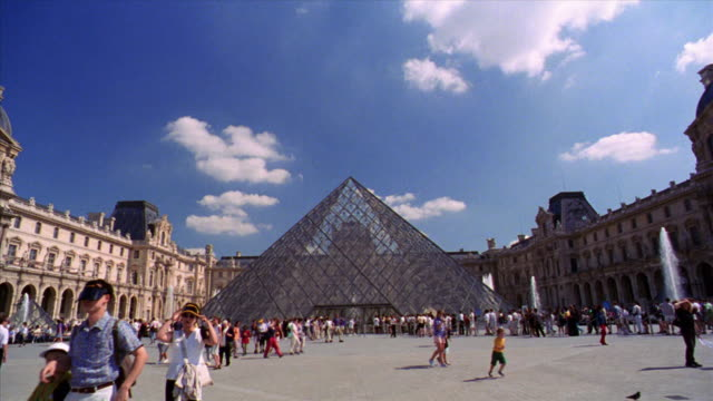 slow motion walking point of view through courtyard of louvre with crowd towards glass pyramide / pan crowd / paris - louvre stock videos and b-roll footage