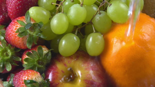 slow motion washing mix fruit in wooden bowl. - fruit bowl stock videos and b-roll footage