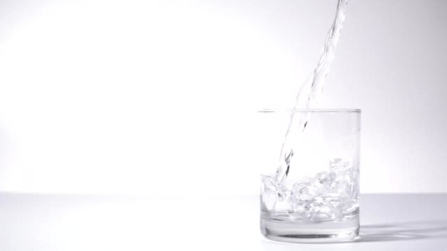 slow motion: water pouring into drinking glass
