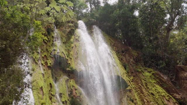 vídeos y material grabado en eventos de stock de slow motion: waterfall cascading down mossy cliff among green vegetation in el limon, dominican republic - hispaniola