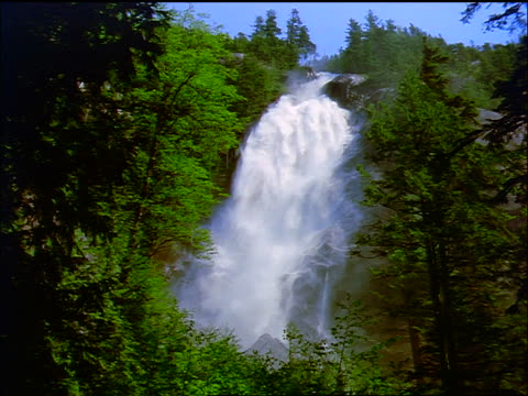 slow motion waterfall with forest in foreground / cascade mountain, banff national park, canada - naturwunder stock-videos und b-roll-filmmaterial