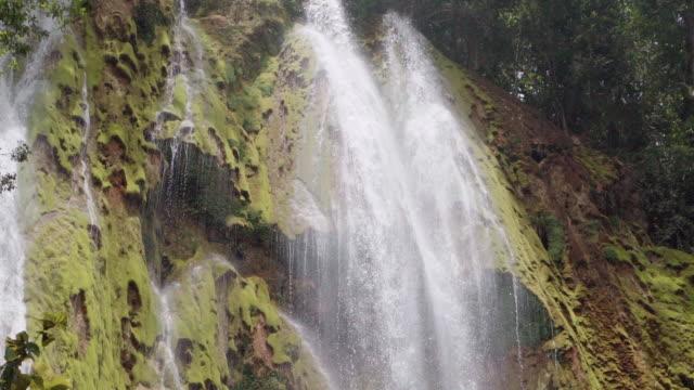 vídeos y material grabado en eventos de stock de slow motion: waterfall with multiple cataracts cascading down green mossy cliff in el limon, dominican republic - hispaniola