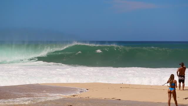 vídeos de stock, filmes e b-roll de slow motion wave breaking, pipeline, hawaii with three men & a woman watching - pipeline wave
