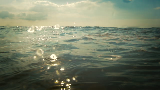 vidéos et rushes de slow motion waves at sea level, surface level and a sunset with waves. - vue du sol