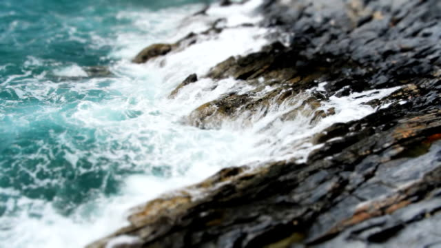 vídeos de stock e filmes b-roll de câmara lenta ondas batendo costa de pedra - soft focus