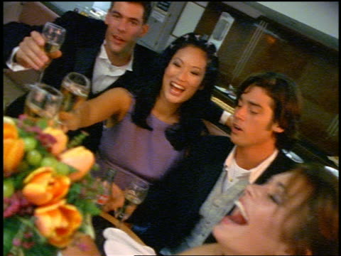 slow motion wedding party laughing + toasting around table in bowling alley snack bar - wedding guest stock videos and b-roll footage