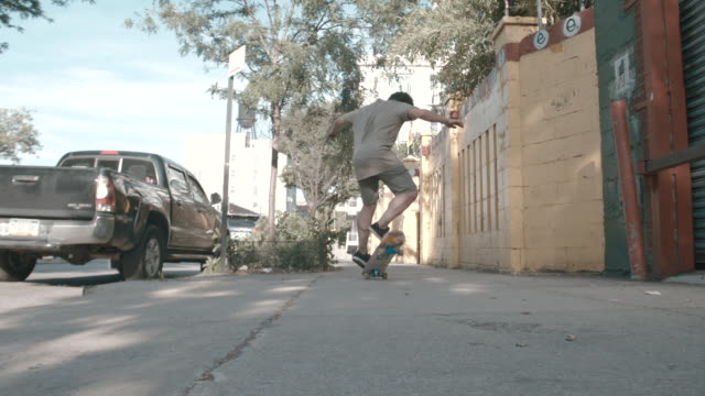 A slow motion, wide angle shot of a young man skateboarding through the streets of Brooklyn, NYC
