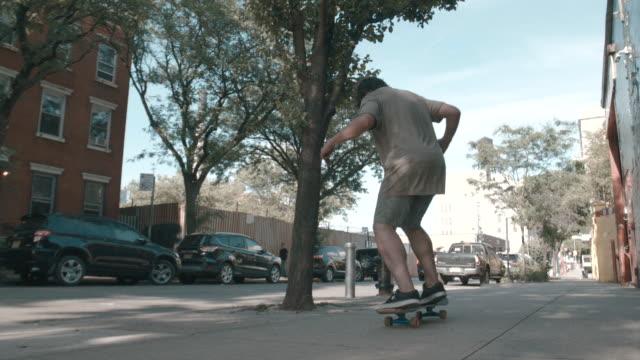 vídeos y material grabado en eventos de stock de a slow motion, wide angle shot of a young man skateboarding through the streets of brooklyn, nyc - sólo hombres jóvenes