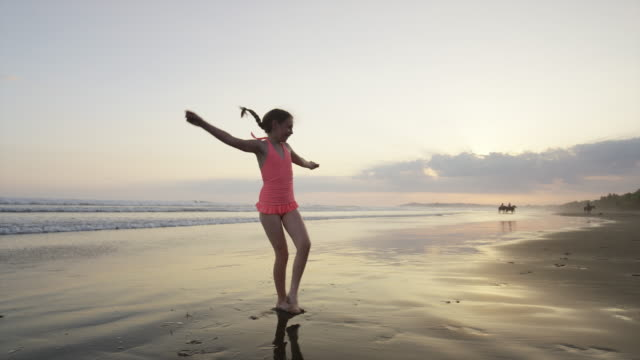 """Slow motion wide panning shot of girl doing cartwheel on beach / Esterillos, Puntarenas, Costa Rica"""