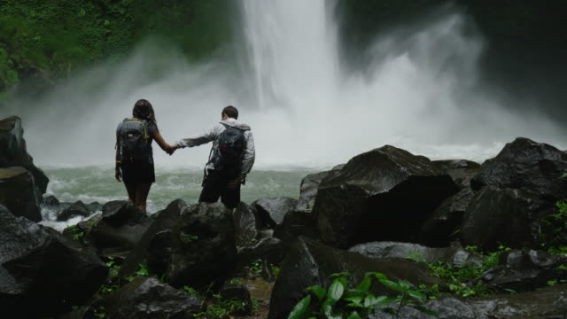 Slow motion wide panning shot of hiking couple admiring waterfall in rain forest / Arenal, La Fortuna, Costa Rica