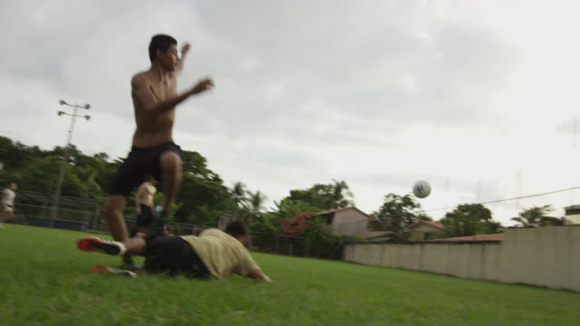 Slow motion wide panning shot of soccer player scoring goal and cheering / Esterillos, Puntarenas, Costa Rica