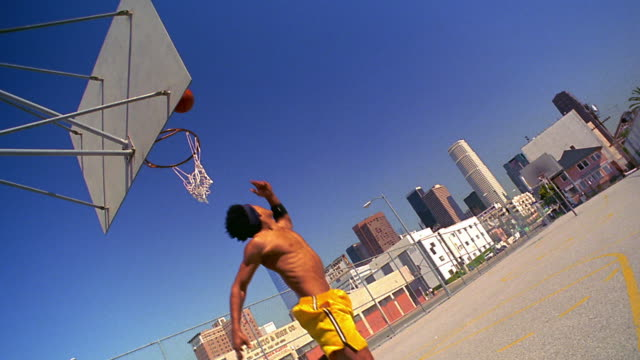 slow motion wide shot black man missing lay-up shot + posing with attitude to cam on outdoor court / los angeles - basketball player stock videos & royalty-free footage